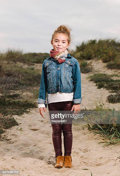 Spain, Galicia, Ferrol, smiling girl in beach dune