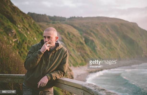 spain, galicia, valdovino, man smoking a cigarette at the coast - 35 39歳 ストックフォトと画像