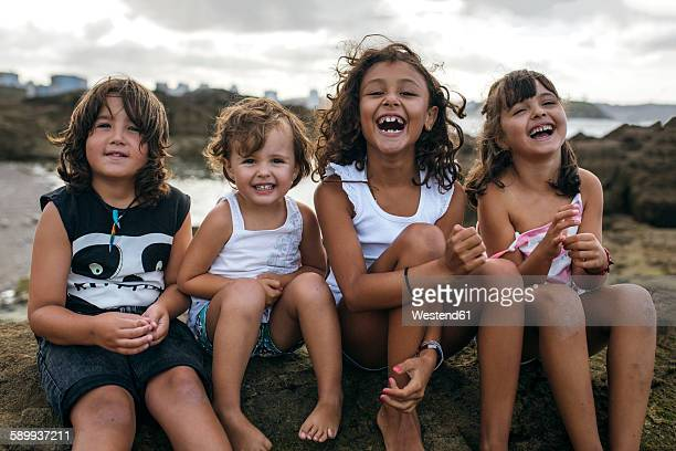 Spain, Gijon, group picture of four little children sitting at rocky coast having fun