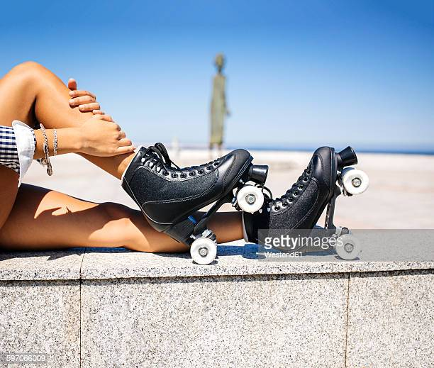Spain, Gijon, legs of a teenage girl with roller skates sitting on a wall