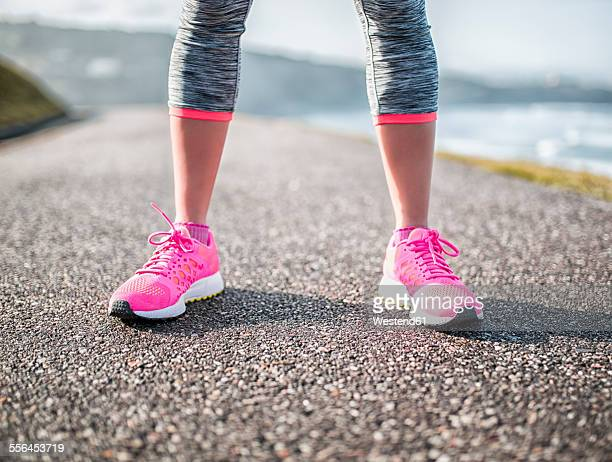 Spain, Gijon, legs of sportive young woman on path