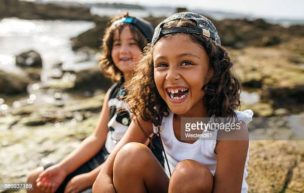 Spain, Gijon, portrait of laughing little girl and her friend in the background sitting at rocky coast