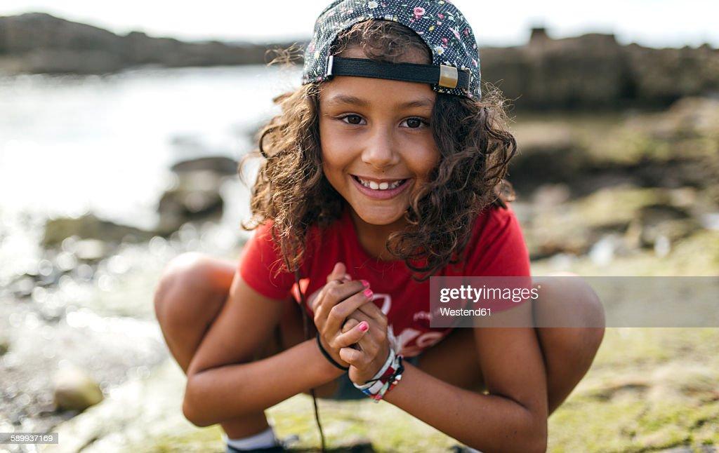 Spain, Gijon, portrait of smiling little girl crouching at rocky coast : Stock Photo