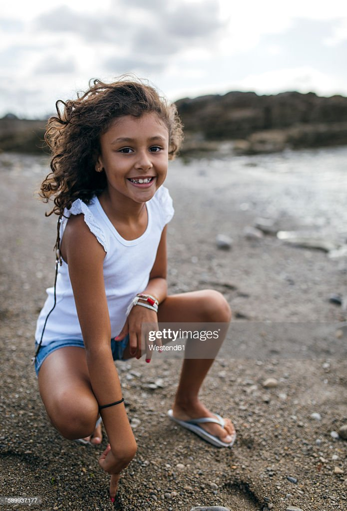 Spain gijon portrait of smiling little girl crouching on for Beautiful small teen