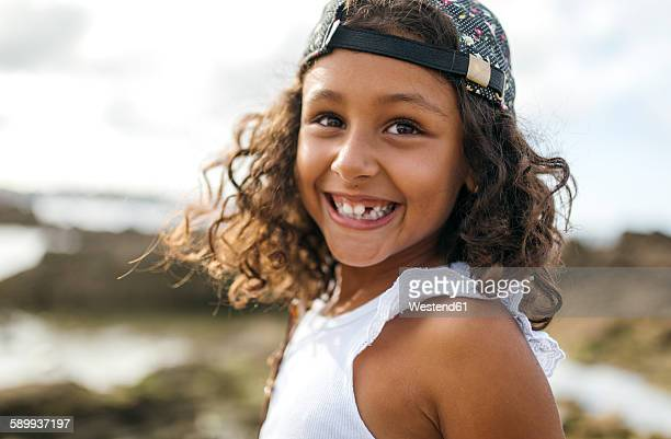 Spain, Gijon, portrait of smiling little girl with tooth gap at rocky coast