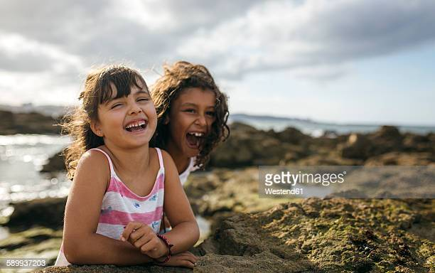 Spain, Gijon, portrait of two laughing little girls at rocky coast
