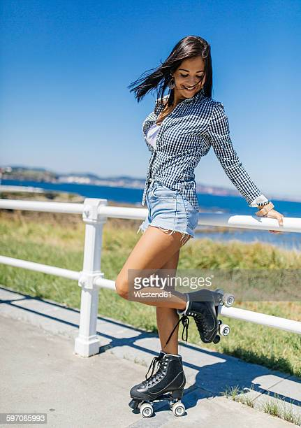 spain, gijon, smiling teenage girl with roller skates - hot pants stock pictures, royalty-free photos & images