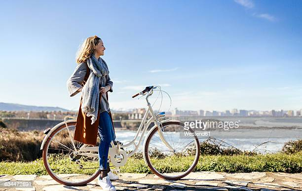 spain, gijon, smiling young woman on bicycle at the coast - ヒホン ストックフォトと画像