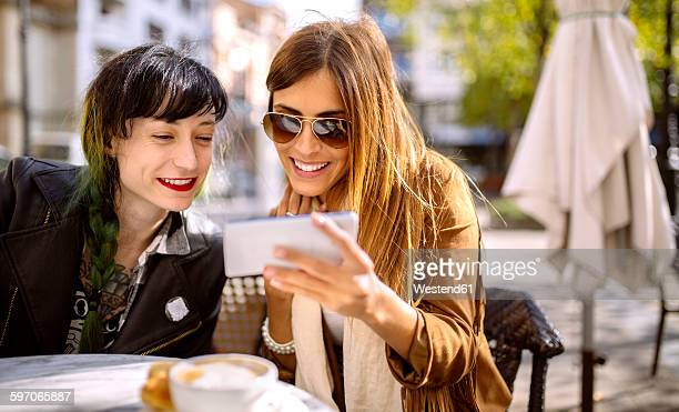 Spain, Gijon, Two friends in cafe looking at smart phone