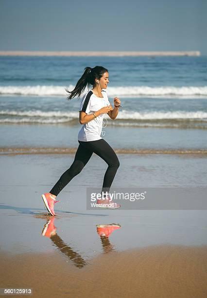 Spain, Gijon, young woman running on the beach