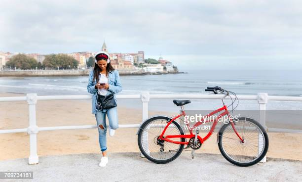 Spain, Gijon, young woman with cell phone and headphones at waterfront promenade