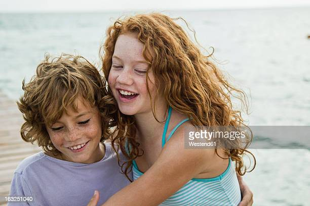 Spain, Girl and boy at the sea, smiling