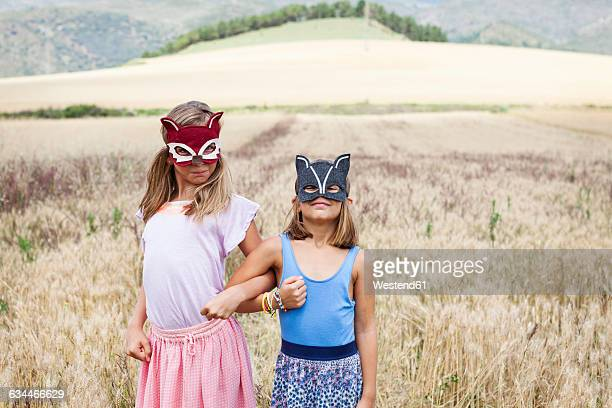 spain, girona, two sister playing with animal masks in nature - arm in arm stock pictures, royalty-free photos & images