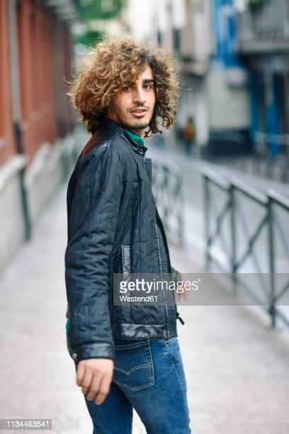 spain, granada, portrait of young man with curly hair walking on pavement - drehen stock-fotos und bilder