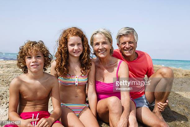 Spain, Grandparents with grandchildren sitting at beach, smiling, portrait
