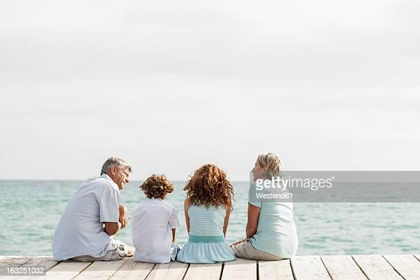 Spain, Grandparents with grandchildren sitting on jetty