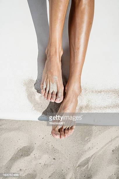 Spain, Human legs on beach towel