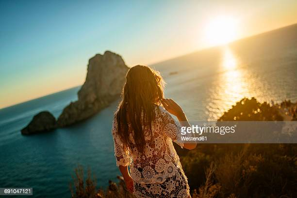 spain, ibiza, woman looking at the sea and es vedra island at sunset - insel ibiza stock-fotos und bilder