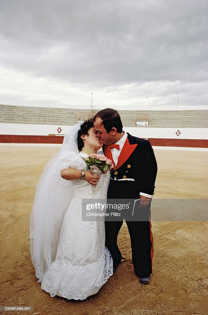 spain just married midget couple kissing in bullring stock