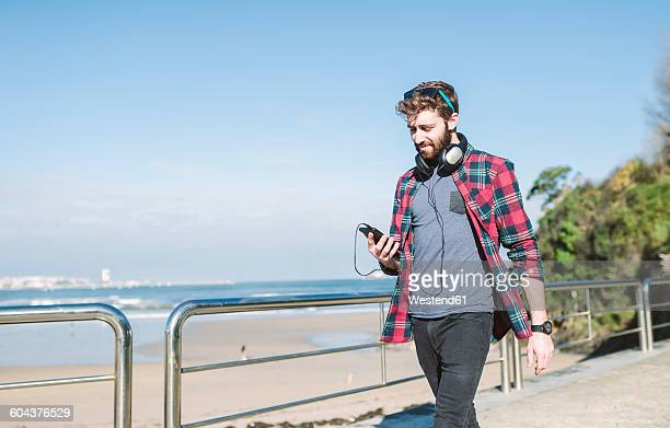 Spain, La Coruna, hipster with headphones looking at his smartphone