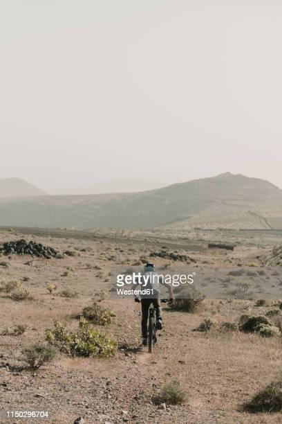 spain, lanzarote, mountainbiker on a trip in desertic landscape - isla de lanzarote fotografías e imágenes de stock