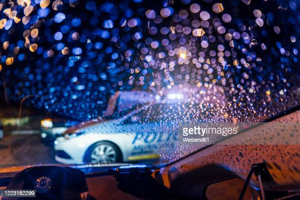 spain, madrid, interior of car parked in front of patrolling police car at night - police car stock pictures, royalty-free photos & images