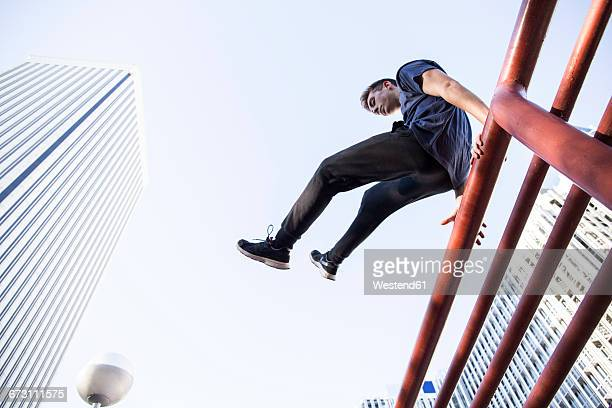 Spain, Madrid, man jumping over a fence in the city during a parkour session