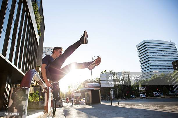spain, madrid, man jumping over a fence in the city during a parkour session - le parkour stock-fotos und bilder