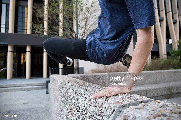 spain, madrid, man jumping over a wall in the city during a parkour session - le parkour stock-fotos und bilder