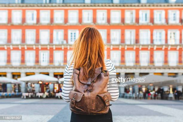 spain, madrid, plaza mayor, back view of redheaded young woman with backpack in the city - madrid fotografías e imágenes de stock