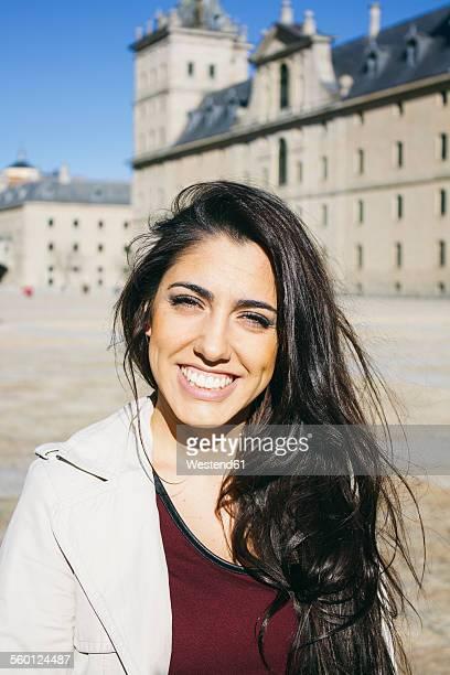 Spain, Madrid, portrait of smiling woman in front of El Escorial