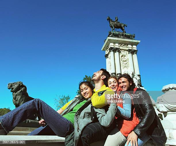 Spain, Madrid, Retiro Park, four friends at the Alfonso XII monument