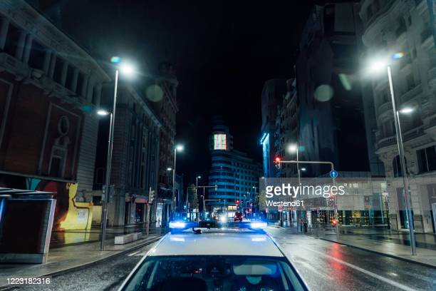 spain, madrid, roof of police car driving along city street at night - police car stock pictures, royalty-free photos & images