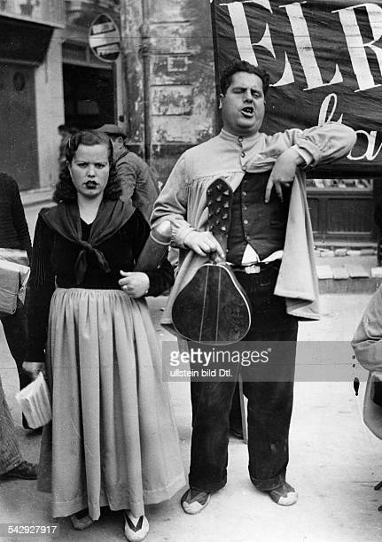 Spain Madrid Spanish Civil War Street musicians supporting the Republican defenders of the city the woman is carrying a dummy grenade under her arm...