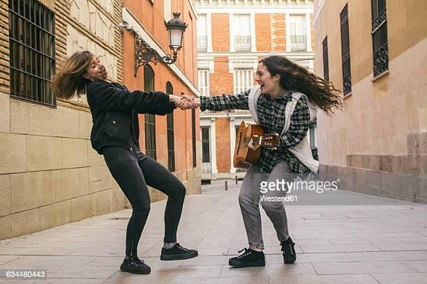 Spain, Madrid, two women dancing in a street