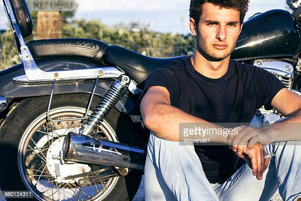 Spain, Madrid, young man sitting next to his motorbike at sunset
