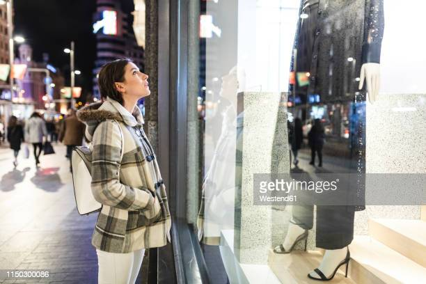 spain, madrid, young woman in the city at night next to gran via looking at a window shop - shop window stock pictures, royalty-free photos & images