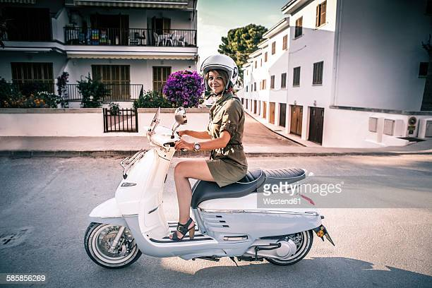 Spain, Majorca, Alcudia, woman on motor scooter