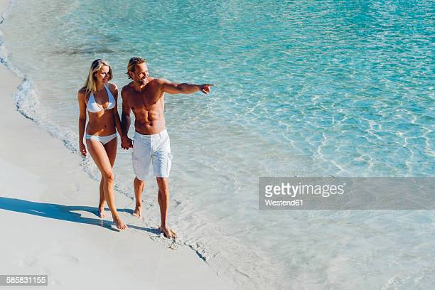 Spain, Majorca, couple walking on the beach with man pointing finger