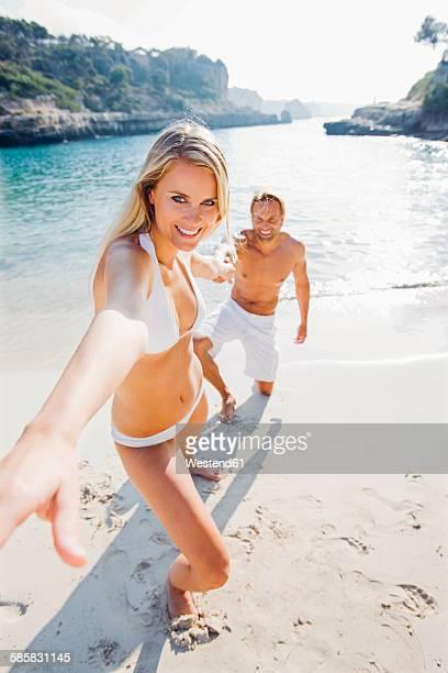 Spain, Majorca, woman pulling mans hand on beach