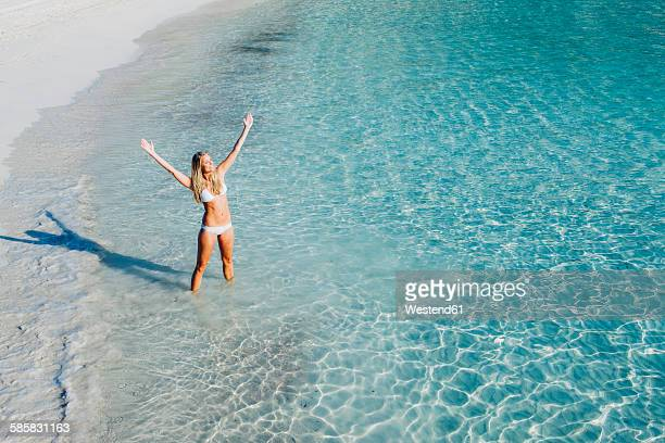 spain, majorca, woman standing in the sea with her arms outstretched - balearic islands stock pictures, royalty-free photos & images