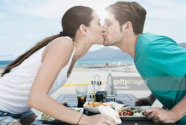 Spain, Majorca, Young couple kissing at dinner near beach