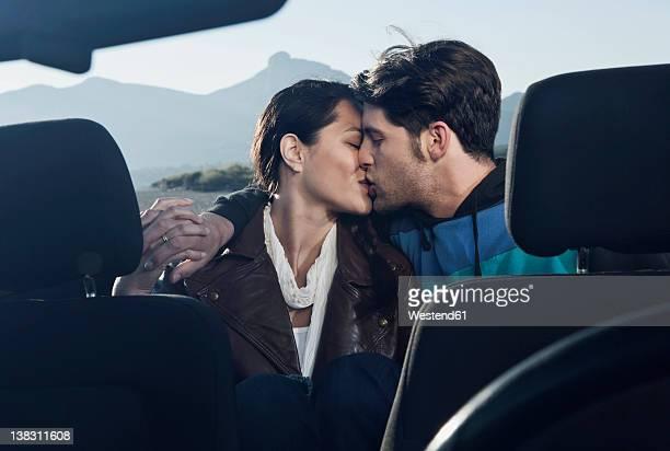 spain, majorca, young couple kissing each other in cabriolet car, close up - embrasser sur la bouche photos et images de collection