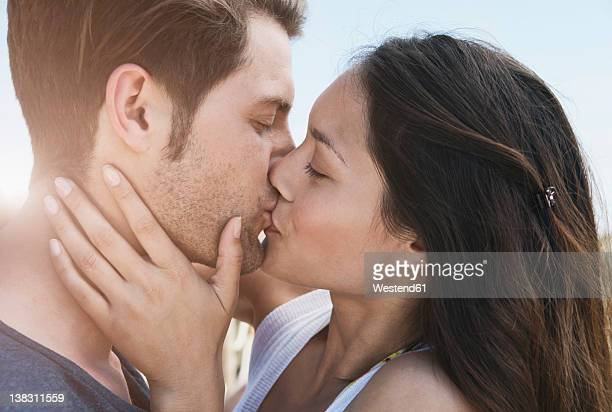 spain, majorca, young couple kissing on boardwalk, close up - bacio sulla bocca foto e immagini stock