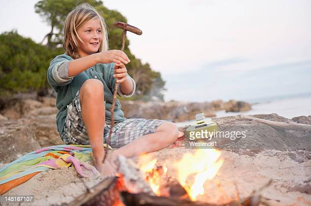 spain, mallorca, boy barbecueing sausage on beach, smiling, portrait - snag tree stock pictures, royalty-free photos & images