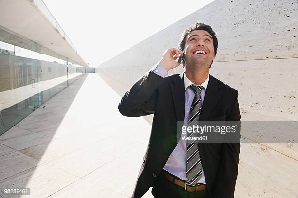 Spain, Mallorca, Businessman using mobile phone, looking up
