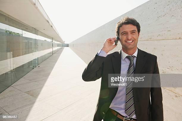 Spain, Mallorca, Businessman using mobile phone, smiling