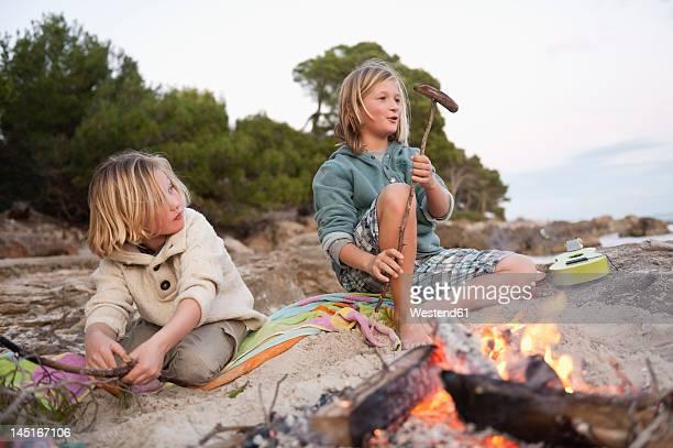 spain, mallorca, children barbecueing sausages on beach - fuego al aire libre fotografías e imágenes de stock