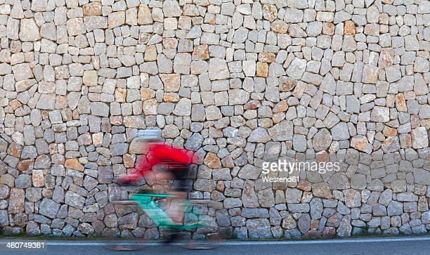 Spain, Mallorca, Cyclist cycling on street at Estellencs