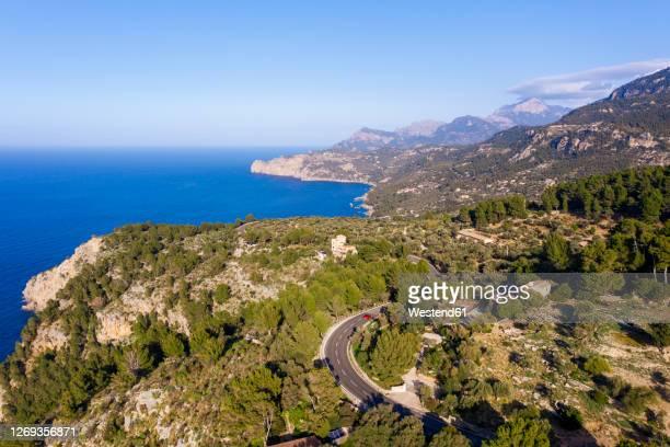spain, mallorca, deia, drone view of coastal highway and surrounding landscape of serra de tramuntana - majorca stock pictures, royalty-free photos & images